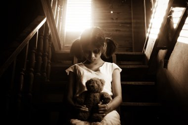 Ghost girl in haunted house holding teddy bear