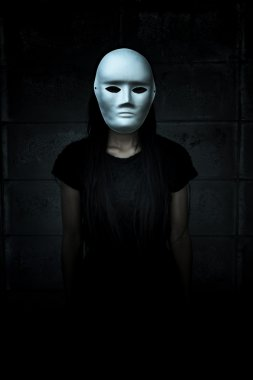 Mysterious woman in black dress wearing white mask