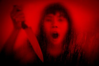 Woman with knife screaming behind stained or dirty window glass