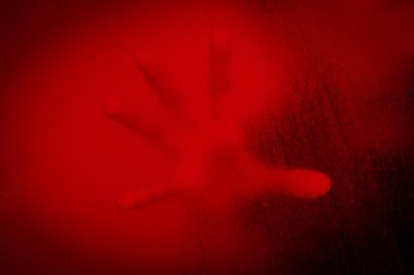 Hand of woman behind stained or dirty window glass