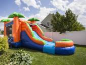 Photo Inflatable bounce house water slide in the backyard