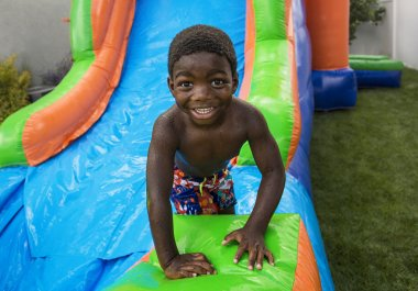 Smiling little boy sliding down an inflatable bounce house.