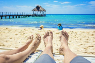 Feet of a couple on lounge chairs