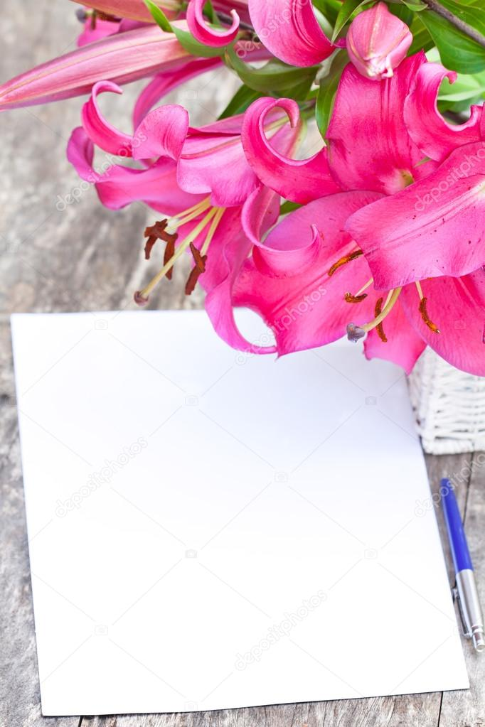 Pink lily Robina flowers bouquet and blank paper sheet with pen ...