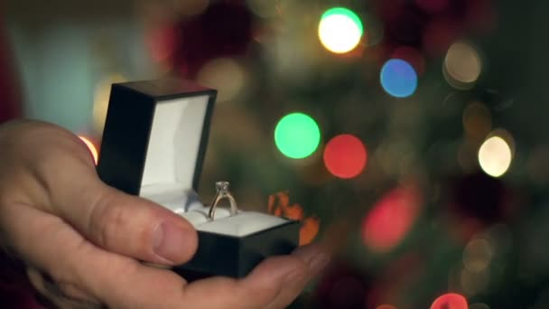 Engagement Ring Proposal Close Up Hands. Blinking Garland. Christmas Tree  Background