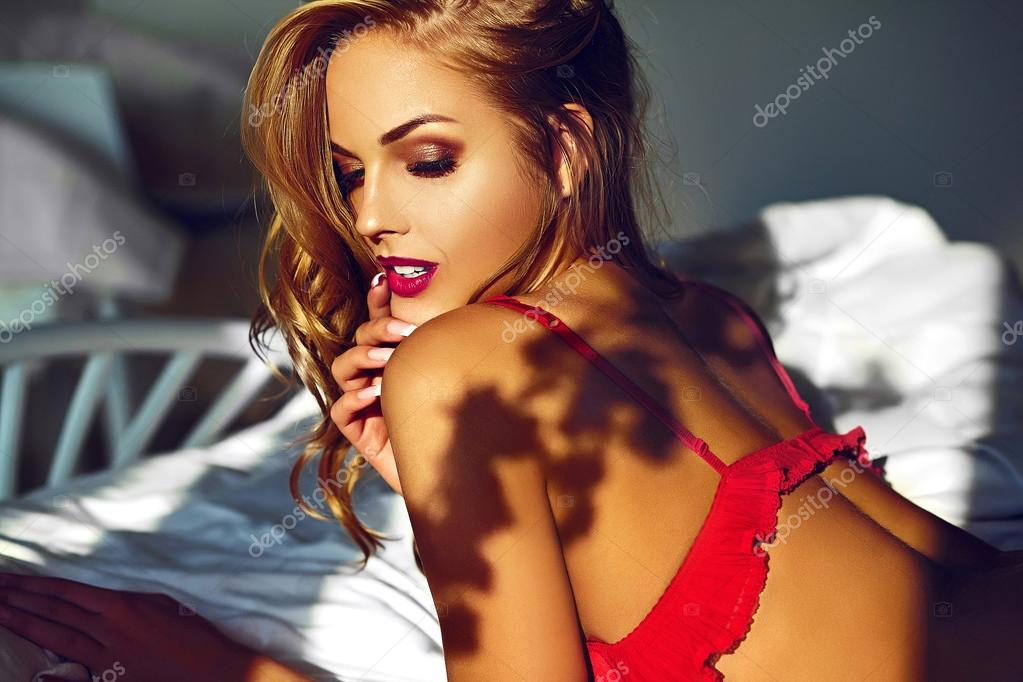 High fashion look.glamor closeup portrait of beautiful sexy stylish  young woman model lying on white bed with bright makeup, with red lips,  with perfect clean skin in red lingerie