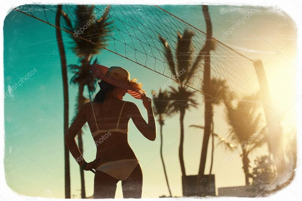 Photo in retro style  of sexy model girl in white bikini with volleyball net on beach and palms behind blue summer sky