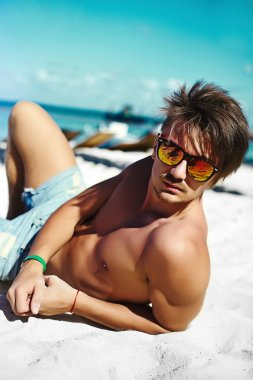 Stylish young sexy hahndsome muscled male model man lying on beach sand enjoying summer travel holiday near ocean in sunglasses
