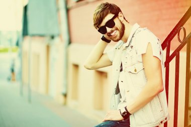 Funny smiling hipster handsome man guy in stylish cloth in the street in sunglasses