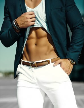 Fashion portrait of young sexy businessman handsome muscled  model man in casual cloth suit in sunglasses in the street showing his  abdominal muscles