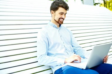 Young man working with laptop, man's hands on notebook computer, business person in casual clothes in the street