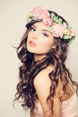 Beautiful Young Woman with Summer Pink Flowers. Long Curly Hair