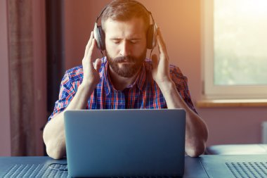 handsome bearded man  in headphones listening to music with lapt