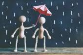 Fotografie Wooden little men under umbrella