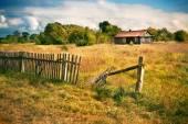 Fotografia Vecchia casa con recinto di legno sul prato vuoto