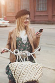 Photo City lifestyle stylish hipster girl with bike using a phone text