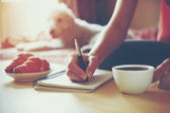 Ženské ruce perem psát na notebooku s ranní káva