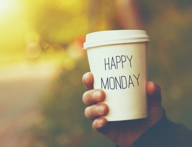 Hand holding paper cup of coffee with Happy Monday text