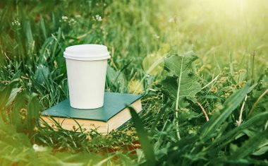 Paper cup of coffee and book in the green grass