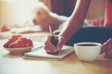 Female hands with pen writing on notebook with morning coffee