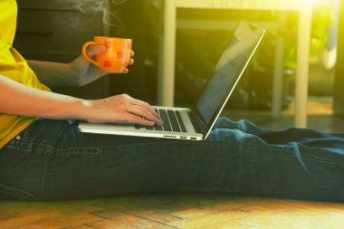 laptop and coffee cup in girls hands sitting on a wooden floor