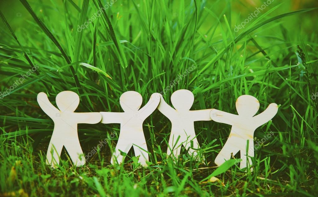 Wooden little men holding hands in summer grass.