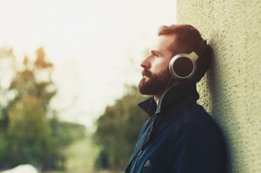 Young stylish bearded man  in headphones listening to music stock vector