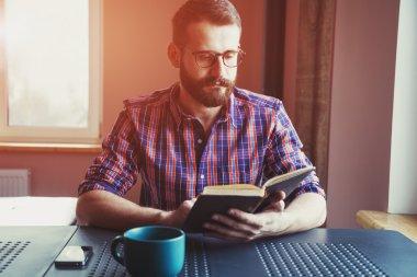 bearded man reading book