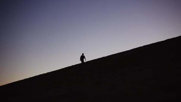 Silhouette Of Male Figure Walking Up Sand Dune