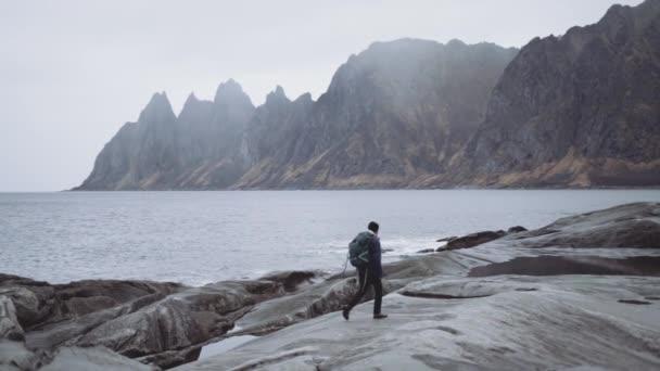 Hiker Walking Along Rocks At Edge Of Fjord