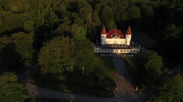 Letecký záběr na krásné sídlo uprostřed lesních stromů a úzká cesta