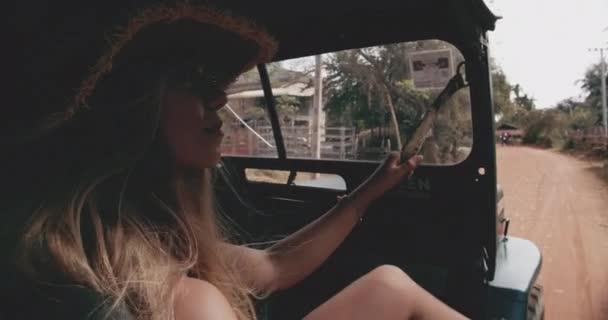 Blondýny půvabné ženské modelky pozoruje vnější straně cestovního džípu