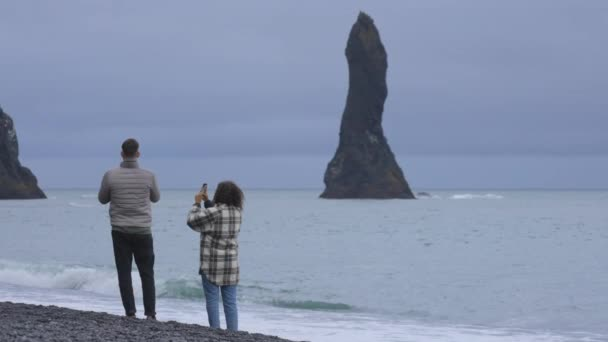 Travelers Appreciating the Scene by Taking Pictures on the Black Sand Beach