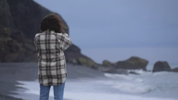 Magnificent Scenery of a Model Standing Still on the Defocused Shot of a Beach
