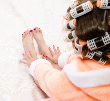 Little girl with manicure and pedicure with hair curlers