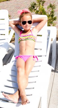 Little girl lying on a chaise lounge and sunbathing