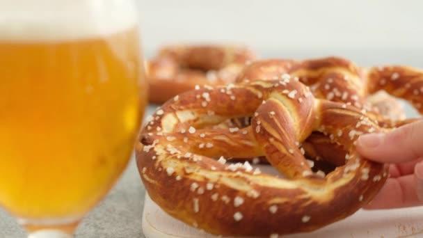 Wiesn-Speisekarte, weiche Brezeln und Bier auf Holzbrett und weißem Hintergrund. Bier wird ausgeschenkt. Vernebeltes Glas mit Bier. Weibliche Hände nehmen Britzel.