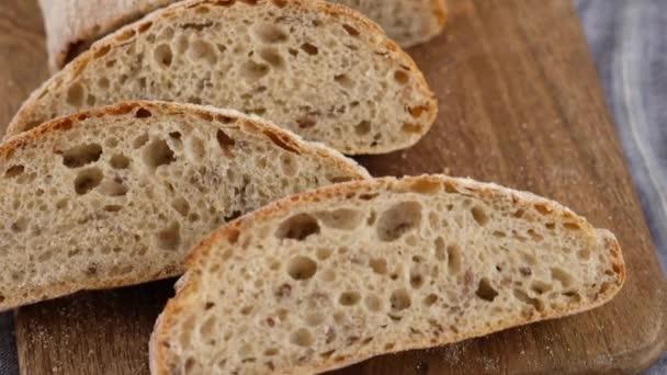 Kameramozgás. Első látásra. A szeletelt kenyér egy fából készült deszkán fekszik. Kenyeret sütök. Megfőzöm a ciabattát. Olasz kenyér. Rozskenyér. 4K