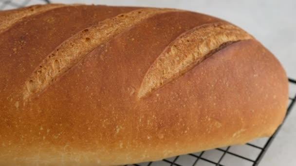 Kameramozgás. A forró búzakenyér közeli képe egy rácson fekszik egy könnyű asztalon. A fehér kenyeret lisztből, vízből, olajból, sóból készült professzionális pékségben készítik..
