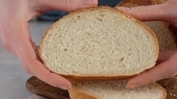 In Großaufnahme drücken weibliche Hände ein Stück Weizenbrot auf ein Holzbrett auf einem hellen Tisch. Weißbrot wird in einer professionellen Bäckerei aus Mehl, Wasser, Öl, Salz zubereitet.