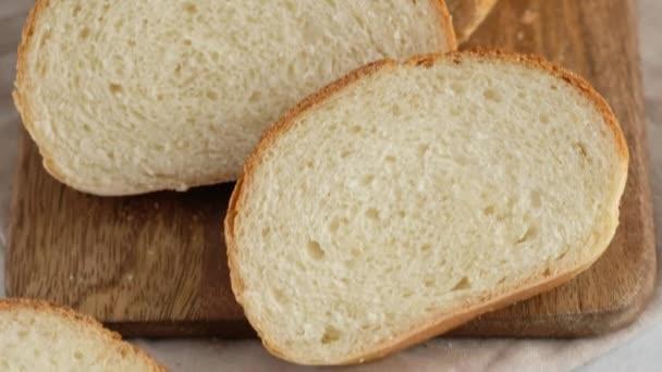 Pohyb kamery. Detailní záběr horkého pšeničného chleba leží na mřížce na lehkém stolku. Bílý chléb se připravuje v profesionální pekárně z mouky, vody, oleje, soli.