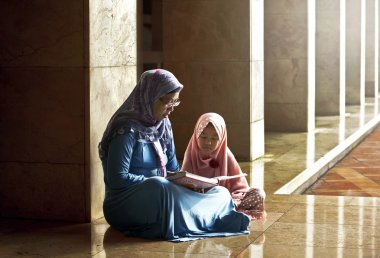 mother teach her daughter reading koran