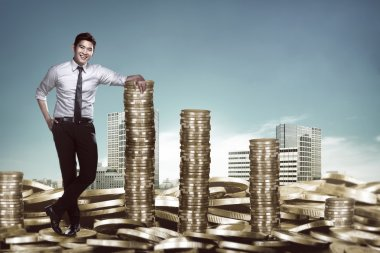 Asian businessman leaning on the stack of coins