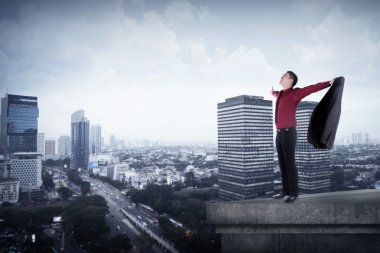 Happy businessman standing on the rooftop