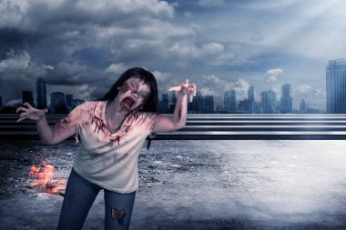 Scary female zombie with burning city background