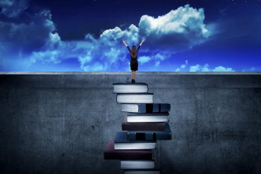Businesswoman standing on the top of the books