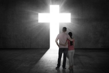 couple looking the shining cross on the wall