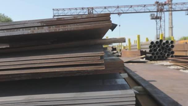 Kovové plechy na kovové skale pod širým nebem, dobré počasí, kovové plechy s portálovým jeřábem v pozadí, sklad kovových výrobků, kovové výrobky