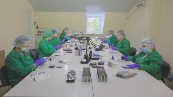 Frauen verpacken Tabletten in einem Paket. Fabrikarbeiter tragen Masken. Arbeit während einer Pandemie