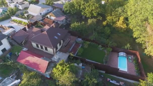 Vidéki ház medencével felülnézetből. Repülni egy gyönyörű ház felett medencével és zöld pázsittal
